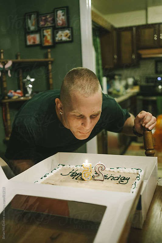 House Party: Mid 20s Man Blows Out Candles On Birthday Cake  by Brian McEntire for Stocksy United