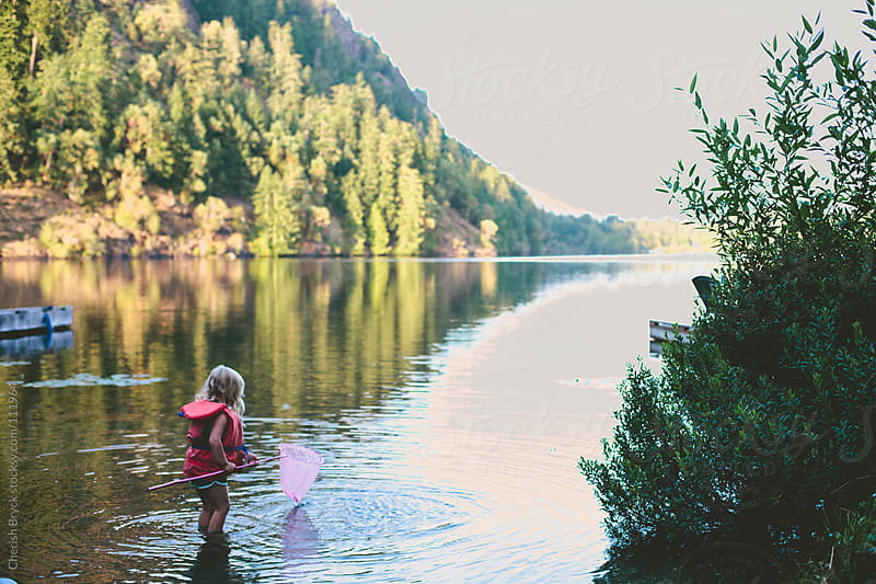 Little girl stands in a lake with her net. by Cherish Bryck for Stocksy United