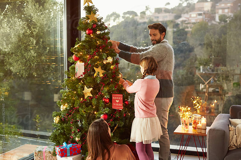Happy Family Decorating Christmas Tree At Home by ALTO IMAGES for Stocksy United