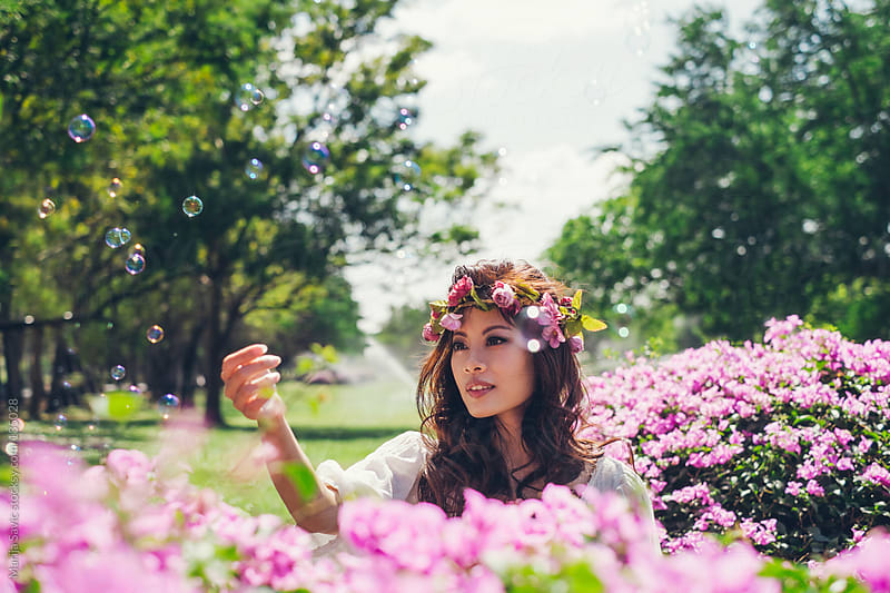 Beautiful asian woman playing with balloons in garden of roses. by Marija Savic for Stocksy United