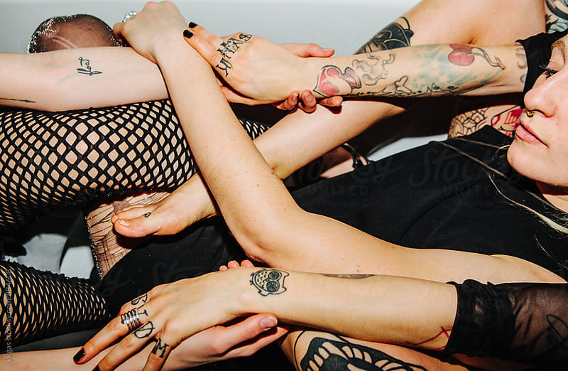 three tattooed women holding hands  by kkgas for Stocksy United