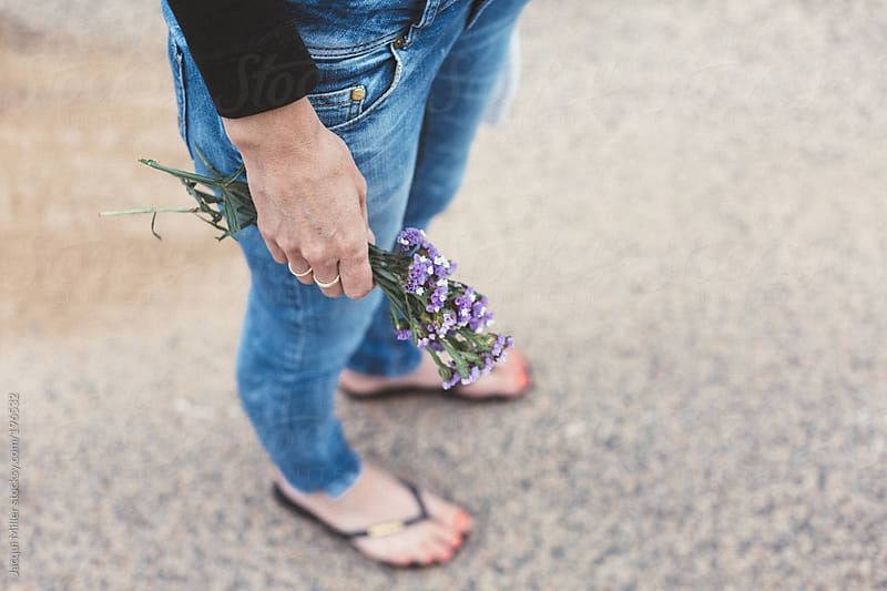 Woman wearing blue denim pants is holding wild flowers in her hand.  by Jacqui Miller for Stocksy United