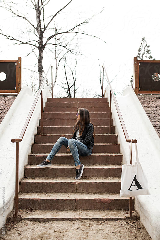 Beautiful woman sitting on the stairs in a park by MEM Studio for Stocksy United