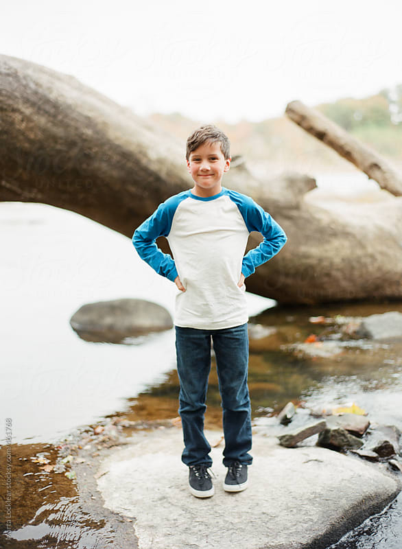 Young boy playing at the river  by Marta Locklear for Stocksy United
