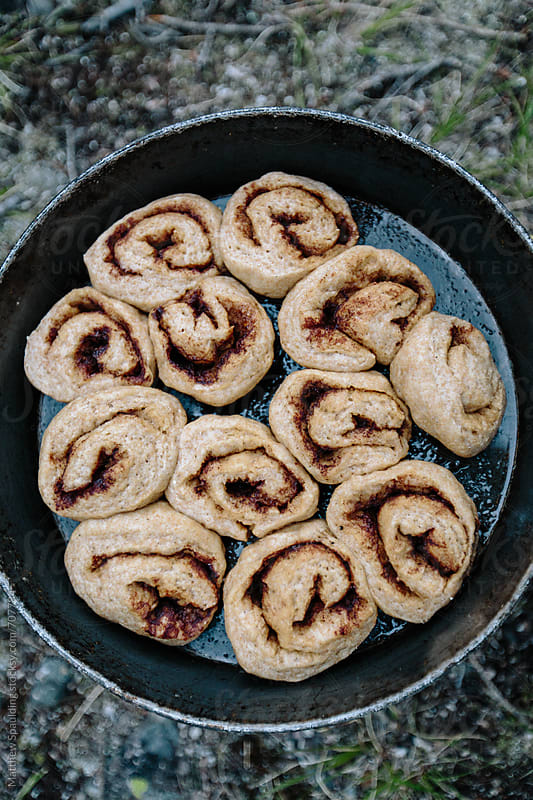 Backcountry cinnamon rolls on camp stove by Matthew Spaulding for Stocksy United