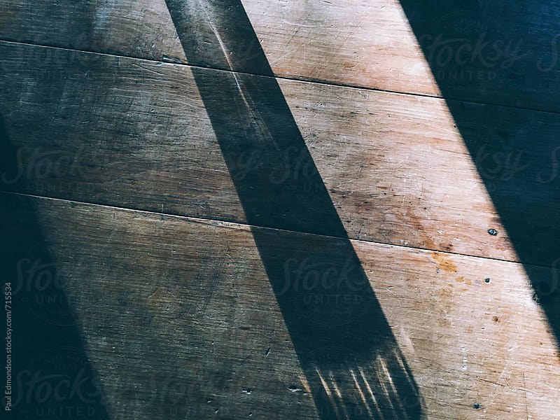 Shadow study on wood table, close up by Paul Edmondson for Stocksy United