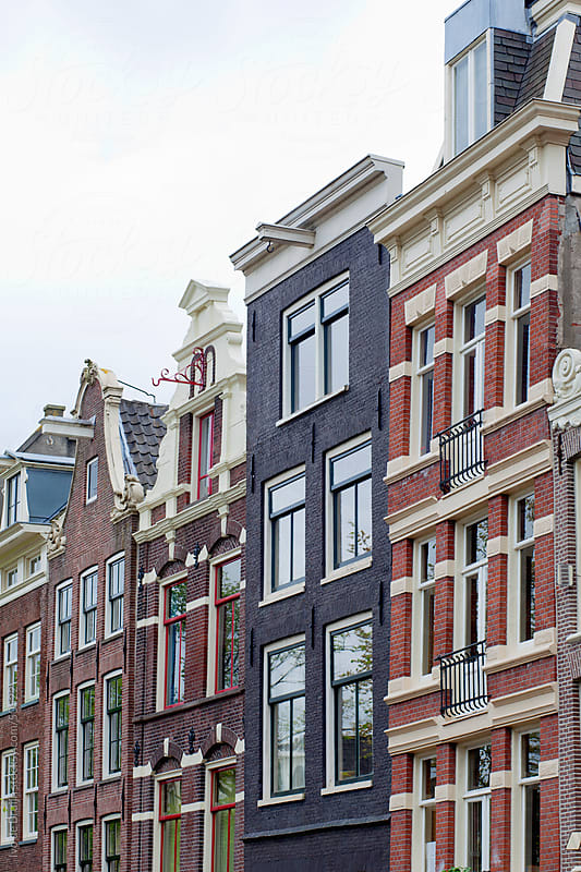 Facades of classic seventeenth century canal houses in Amsterdam by Ivo de Bruijn for Stocksy United