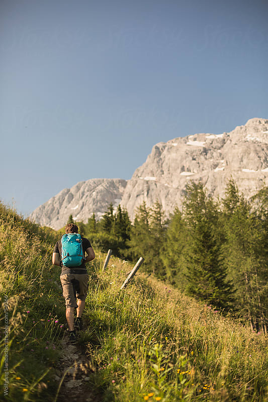 A young man is hiking a trail up a mountain by Wolfgang Lienbacher for Stocksy United