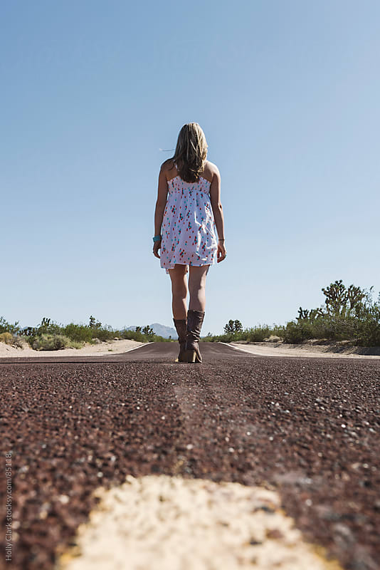A woman walks down the middle of a highway in the desert. by Holly Clark for Stocksy United