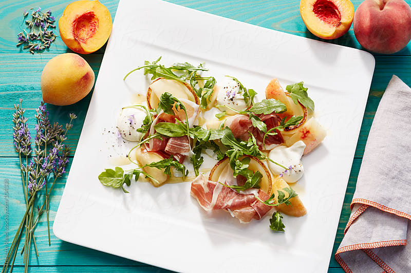 Peach, prosciutto, arugula, pear salad with crème fraîche and lavender  by Trinette Reed for Stocksy United
