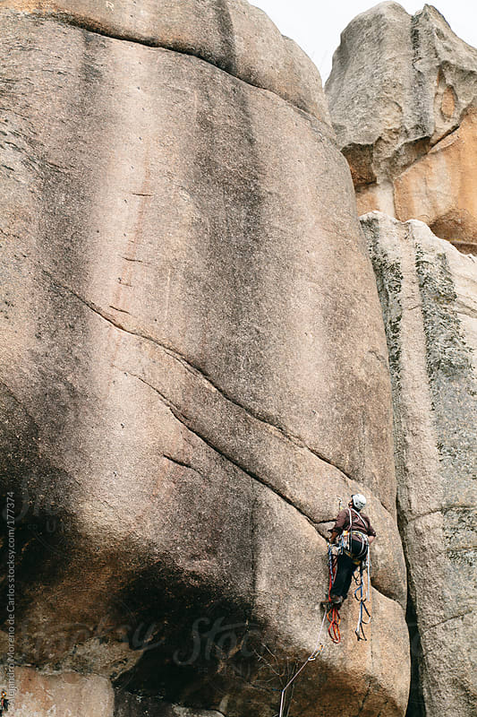 Young man rock climbing a big rock wall by Alejandro Moreno de Carlos for Stocksy United