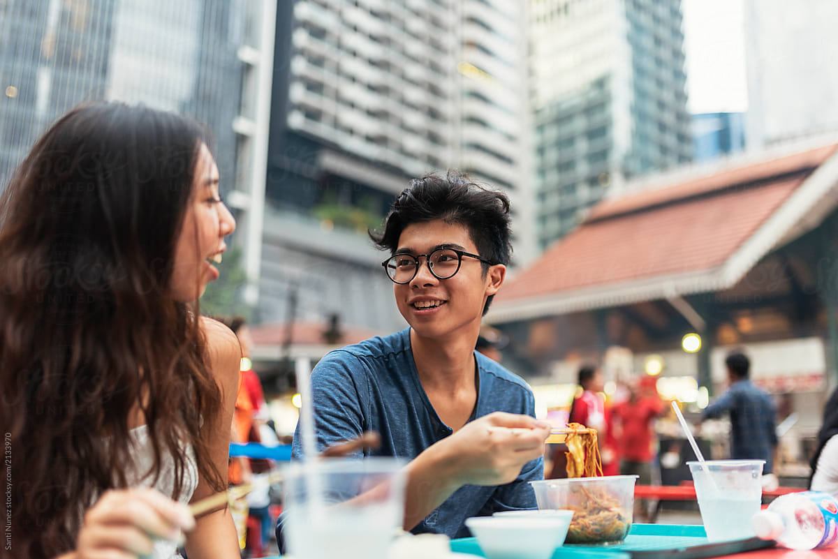 Young Asian Couple Having Dinner In One Hawker by Santi Nuñez