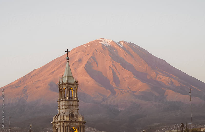 A tower of the Cathedral of Arequipa with the volcano, El Misti, behind in the sunset by Adrian Seah for Stocksy United