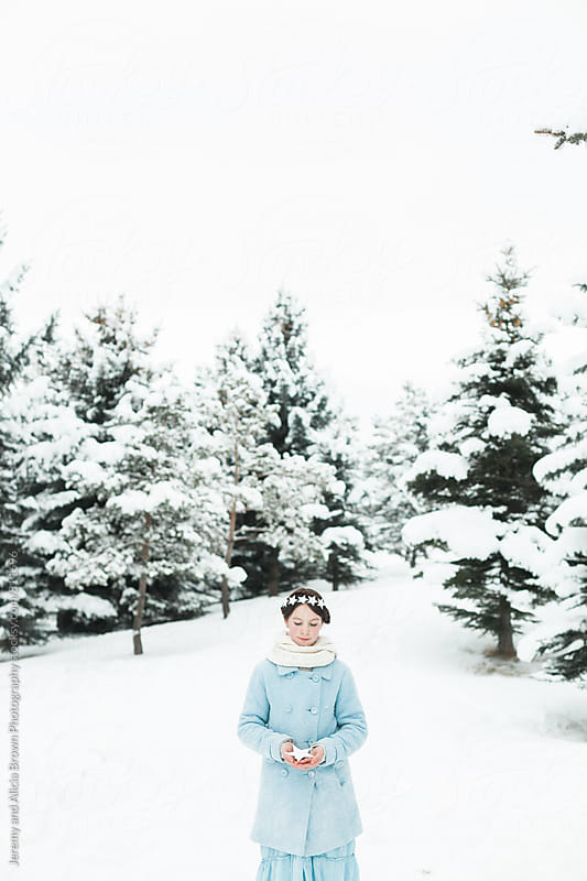 Little girl wearing a star wreath in a wintery scene by Jeremy and Alicia Brown Photography for Stocksy United