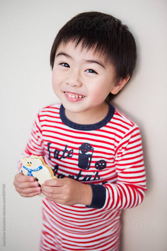 Cute Asian boy eating Santa shaped cookie by Suprijono Suharjoto for Stocksy United