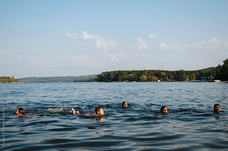 a group of children swimming in a lake by Margaret Vincent for Stocksy United