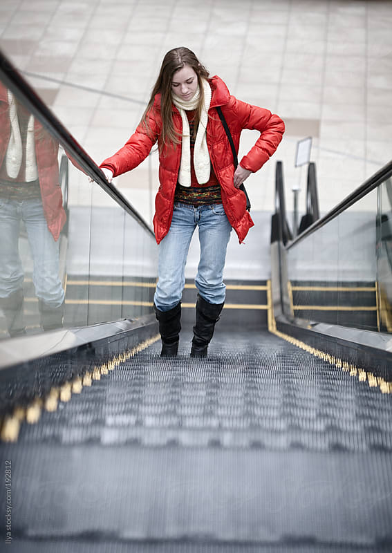 Young woman on the escalator by Ilya for Stocksy United