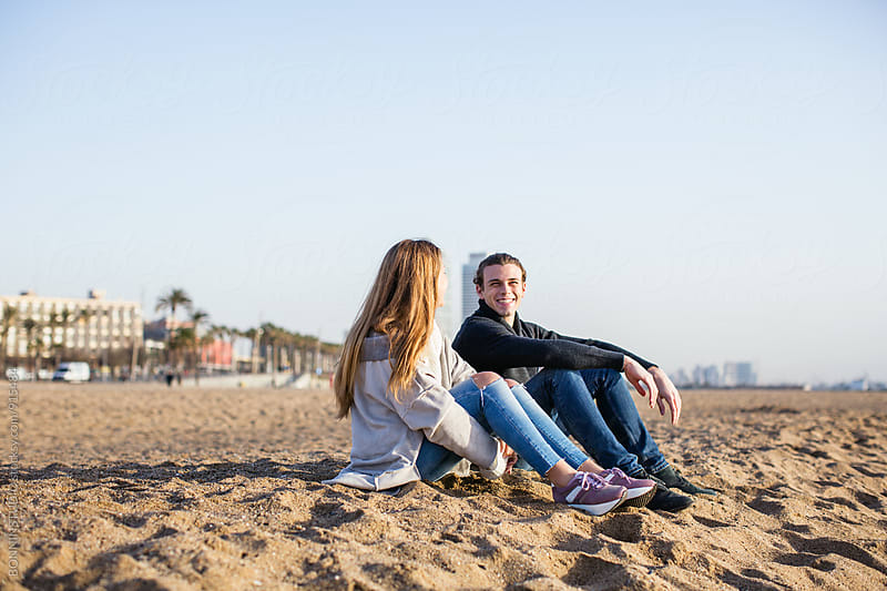 Side view of teen couple sitting on the beach. by BONNINSTUDIO for Stocksy United