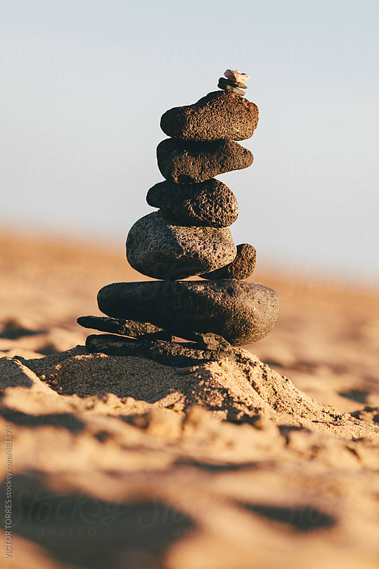 Stones Balanced on Top of Each Other on a Sandy Beach by VICTOR TORRES for Stocksy United