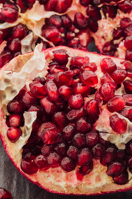 A freshly opened pomegranate fruit by Adam Nixon for Stocksy United