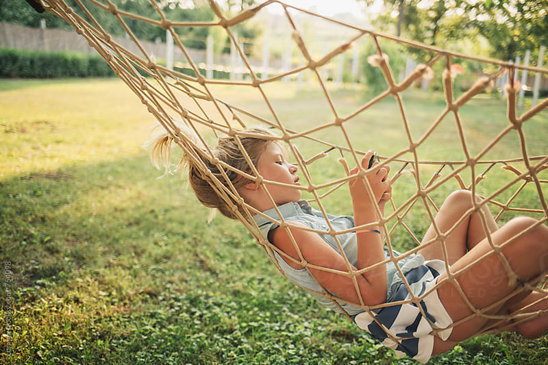Blonde Girl Texting in a Hammock by Lumina for Stocksy United