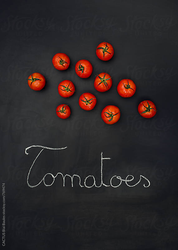 Tomatoes on a chalkboard by Blai Baules for Stocksy United