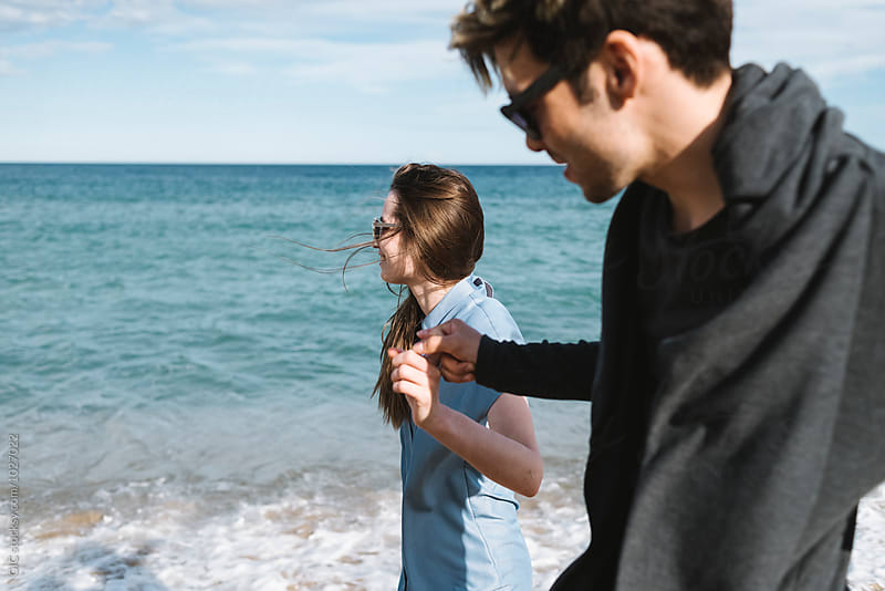 Young couple enjoying the sea by Simone Becchetti for Stocksy United