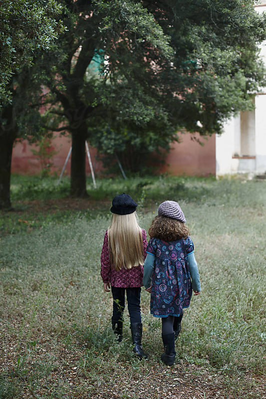 Couple of little fashion girls in a yard with tree by Miquel Llonch for Stocksy United