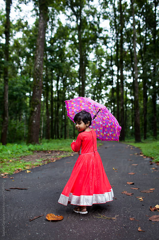 Little girl with umbrella in the forest by Saptak Ganguly for Stocksy United