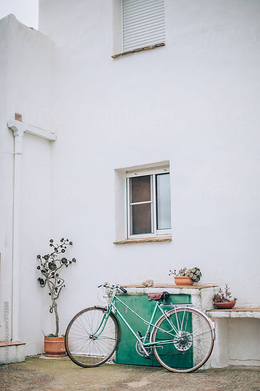 Green vintage bicycle parked outside a picturesque house by Lydia Cazorla for Stocksy United