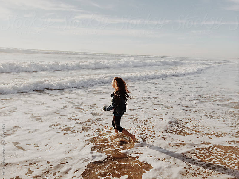 Girl Running Out into the Ocean by Denise Bovee for Stocksy United
