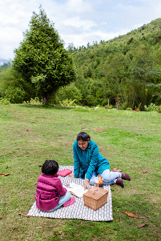 Mother reading a story to her daughter at a picnic in the hills by Saptak Ganguly for Stocksy United