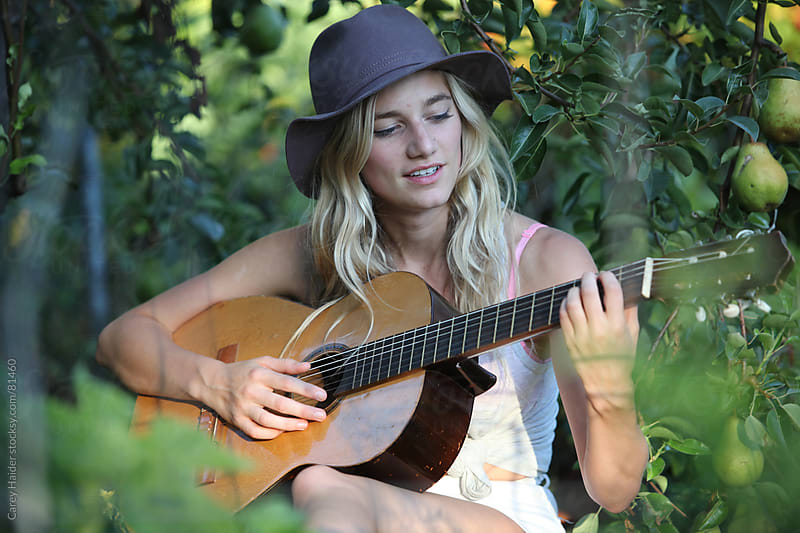 A Youthful Young Beautiful Woman Playing Guitar In A Garden by Carey Haider for Stocksy United