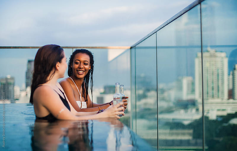 Two girlfriends having fun chat in swimming pool with city skyline behind them. by Marko Milanovic for Stocksy United