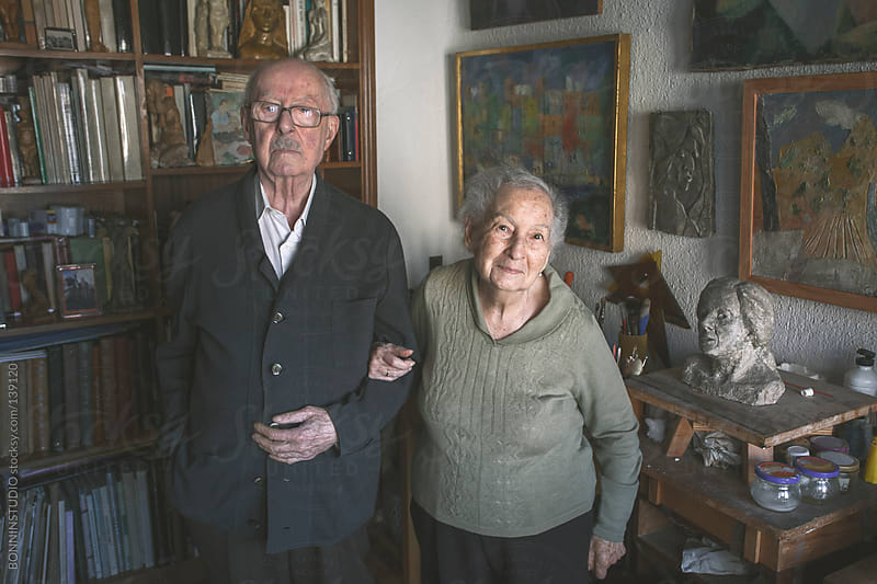 Portrait of old couple standing on artistic studio in home.  by BONNINSTUDIO for Stocksy United