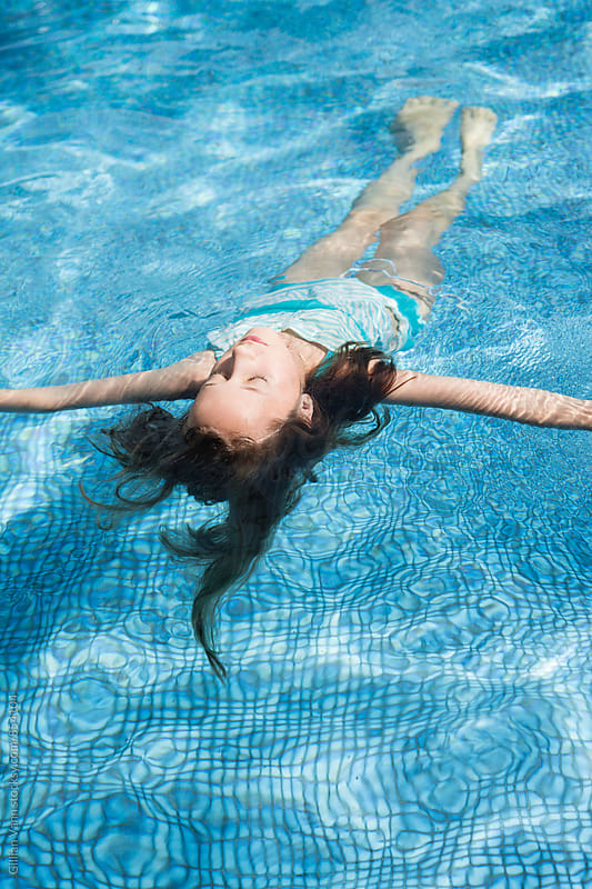 girl floating in swimming pool by Gillian Vann for Stocksy United