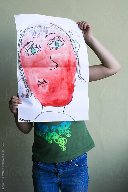 Young girl showing off her self portrait artwork by Carolyn Lagattuta for Stocksy United