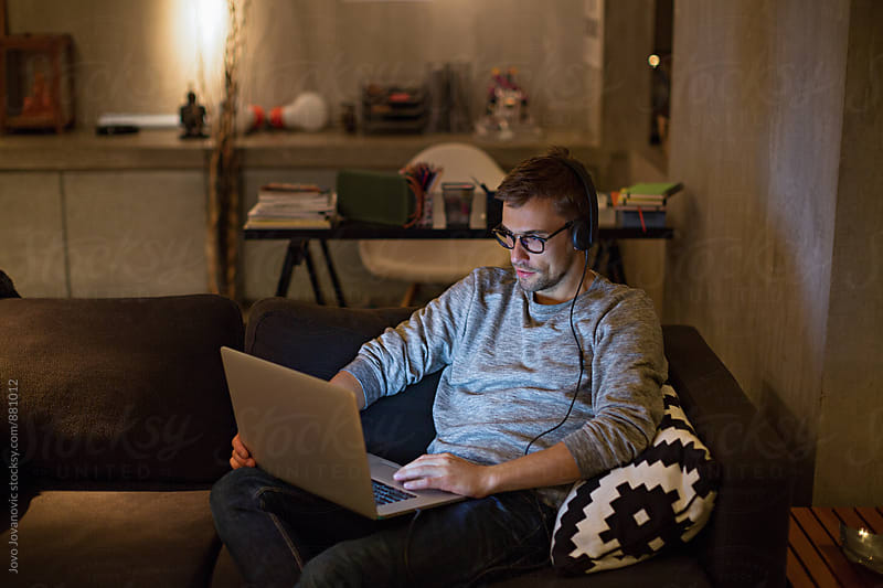Man working from home at night by Jovo Jovanovic for Stocksy United