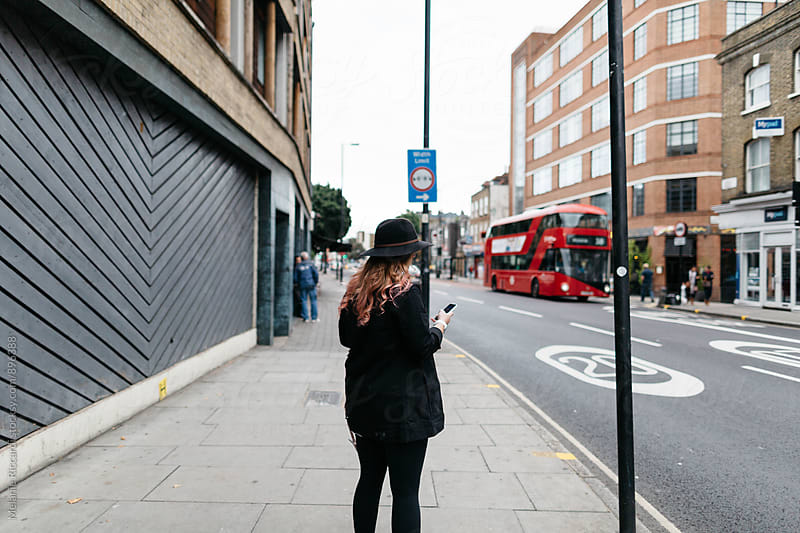 Woman using phone on the street by Melanie Riccardi for Stocksy United