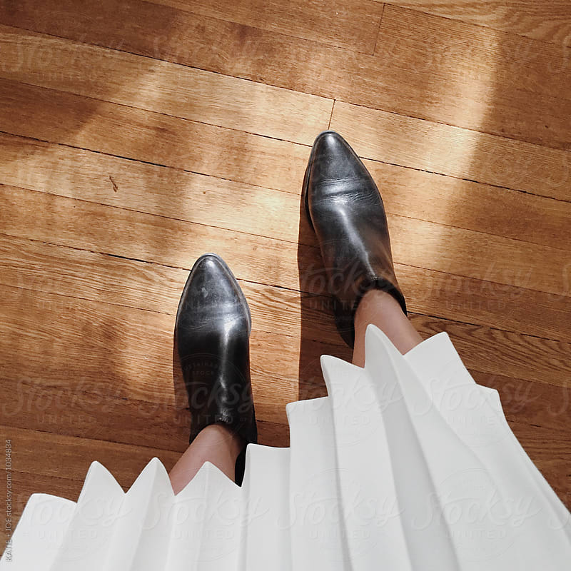 Two feet in boots and a white pleated skirt by KATIE + JOE for Stocksy United