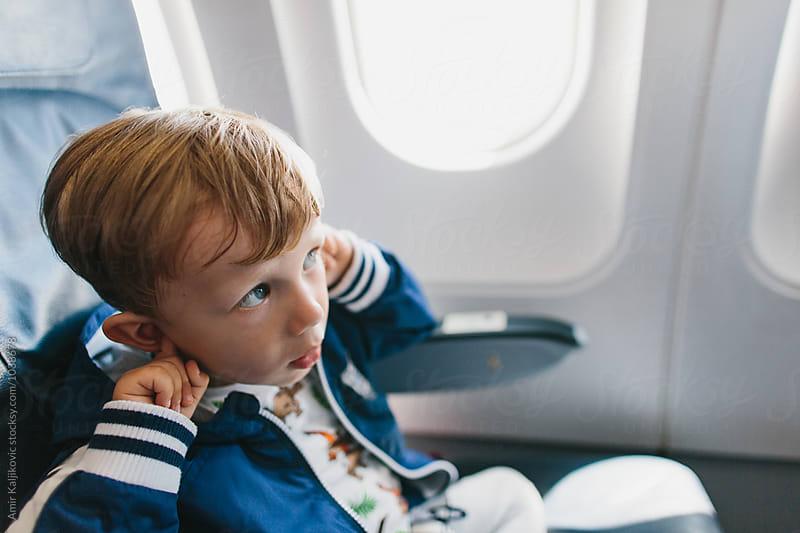 Little boy with fingers in ears on plane by Amir Kaljikovic for Stocksy United
