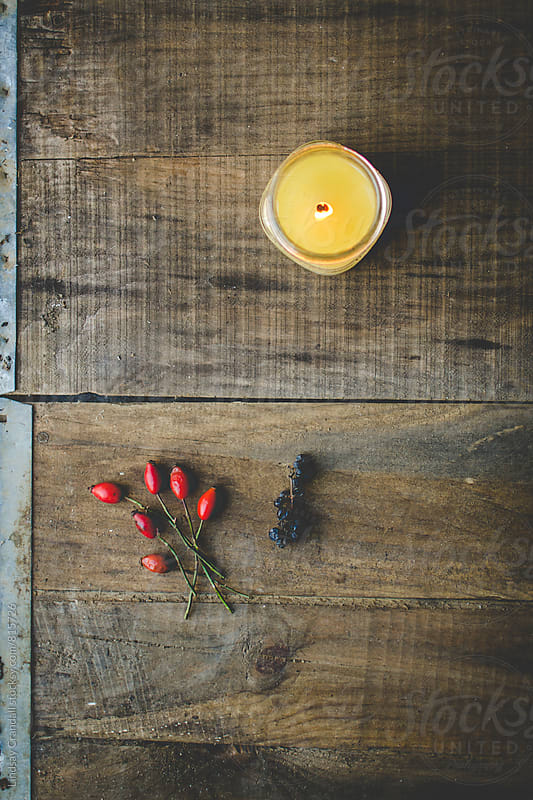 Candle with rose hips and berries on distressed wood by Lindsay Crandall for Stocksy United