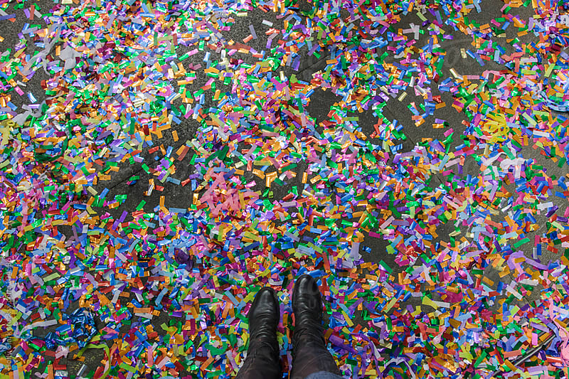 A woman's feet wearing black boots stands amidst colorful confetti. by Holly Clark for Stocksy United