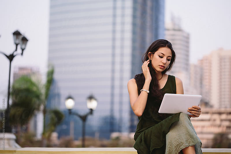 Young woman using notepad outdoors by michela ravasio for Stocksy United
