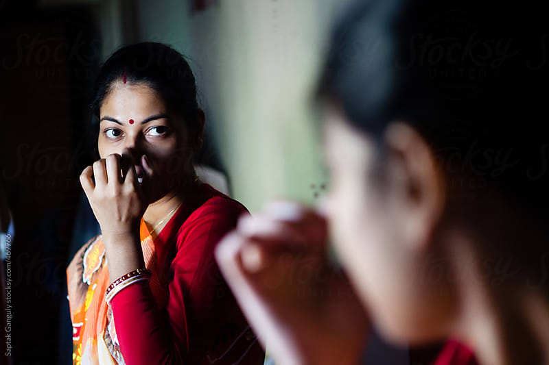 Beautiful woman putting on bindi standing infront of the mirror by Saptak Ganguly for Stocksy United
