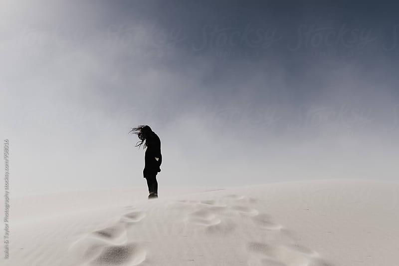 Woman standing alone in windy desert