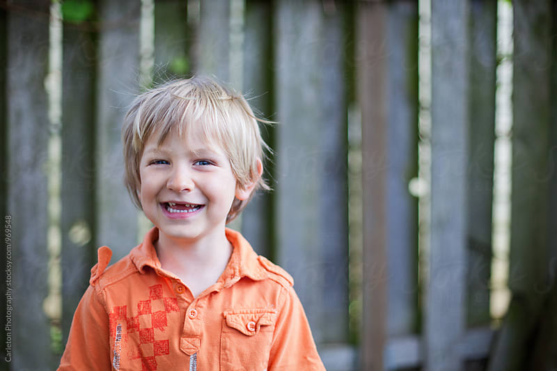 Happy blonde boy with missing front teeth by Carleton Photography for Stocksy United