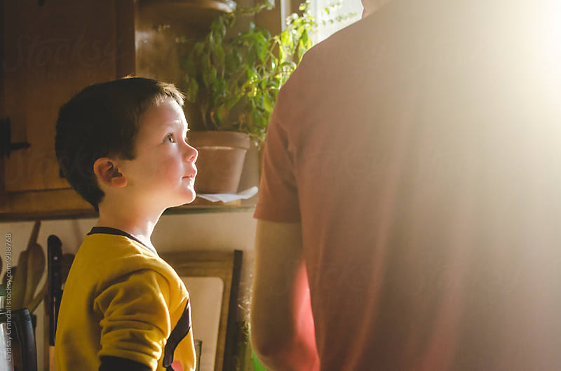 Young boy looking up at his father by Lindsay Crandall for Stocksy United