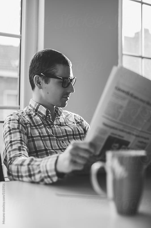 Man Reading Newspaper and Drinking Morning Coffee by Mosuno for Stocksy United