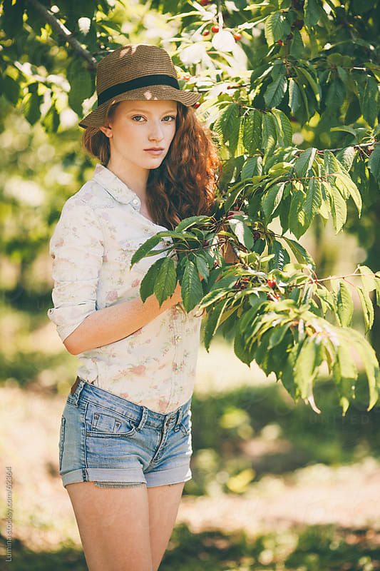 Ginger Woman Standing by a Cherry Tree by Lumina for Stocksy United